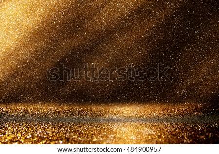glitter vintage lights background. dark gold and black. de focused