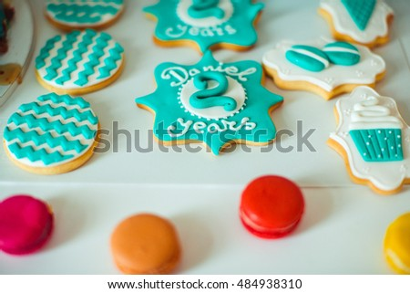 Cookies with glaze lettering 'Daniel 2 years' lie on the sweet-bar #484938310