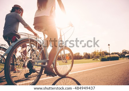 Cycling together. Low angle view of young people riding bicycles along a road together Royalty-Free Stock Photo #484949437