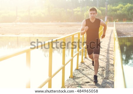 Sporty young man jogger exercising working out at morning outdoors. #484965058