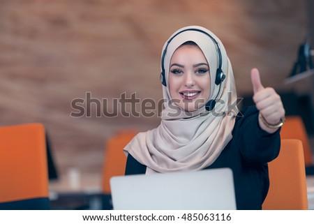 Beautiful phone operator Arab woman working in modern startup office #485063116