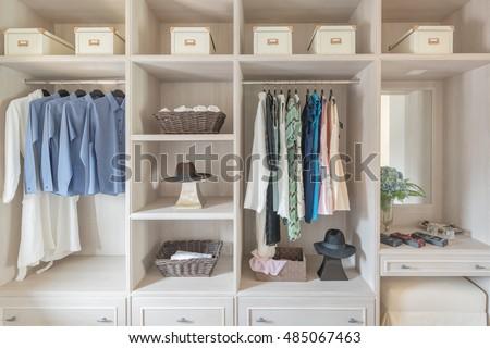 modern wooden wardrobe with clothes hanging on rail in walk in closet design interior #485067463
