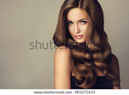 Brunette  girl with long  and   shiny wavy hair .  Beautiful  model with curly hairstyle . Royalty-Free Stock Photo #485071654