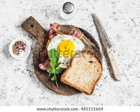 Toast with fried egg, bacon and arugula on the wooden cutting board. Delicious breakfast. On a light background, top view    #485151664