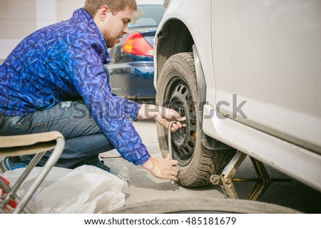 man changing a wheel on the road. on way there was breakage of wheel, puncture, necessary to lift the car jack and remove the wheel by loosening the nuts. road problems travelers. do it yourself #485181679