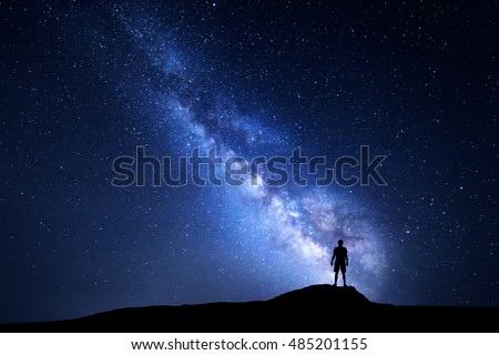 Milky Way. Beautiful night sky with stars and silhouette of a standing alone man on the mountain. Blue milky way with man on the hill. Background with galaxy and silhouette of a man. Universe #485201155