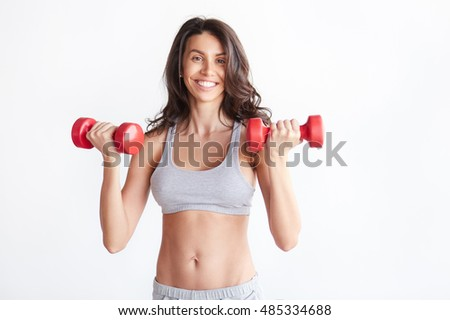 beautiful sporty woman with red dumbbells. Fitness girl lifting weights and smiling isolated over white background #485334688