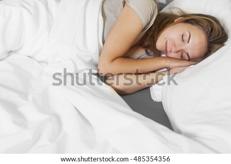 Attractive young woman sleeping in bedroom.  #485354356