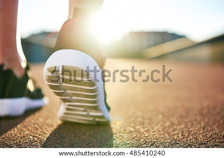 Close up low angle view of running shoes with while soles on an empty road as the sun highlights the distance Royalty-Free Stock Photo #485410240