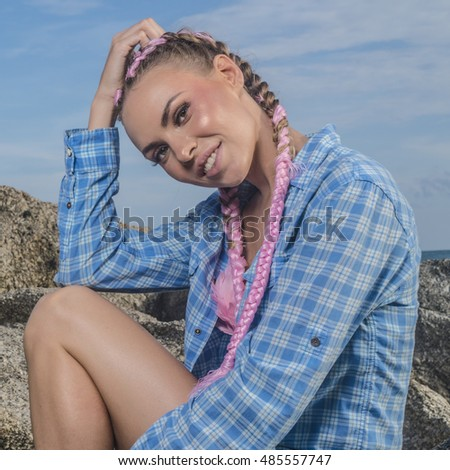 Young pretty girl with pink plaits wearing blue checked shirt smiling and looking into the camera while sitting on the rock during summer day over sky background  #485557747