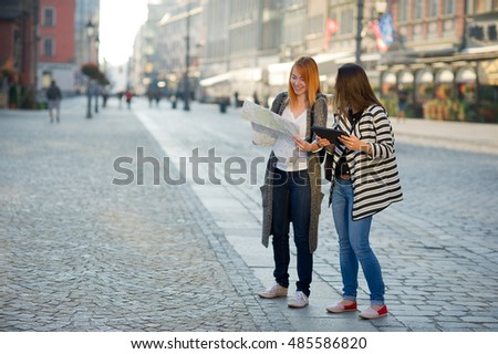 Two young women walk on unfamiliar city. Girlfriends go sightseeing. In hands women have a card. They are surrounded with fine architecture. Tourists have a good mood. #485586820