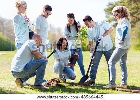 volunteering, charity, people and ecology concept - group of happy volunteers planting tree and digging hole with shovel in park #485664445