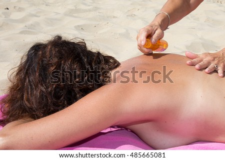 Attractive woman lying at beach with sun protection cream #485665081