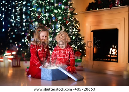 Family on Christmas eve at fireplace. Kids opening Xmas presents. Children under Christmas tree with gift boxes. Decorated living room with traditional fire place. Cozy warm winter evening at home. #485728663