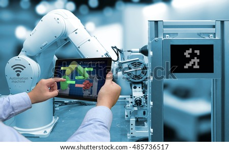 Industry 4.0 concept . Man hand holding tablet with performance check screen software and blue tone of automate wireless Robot arm in smart factory background #485736517