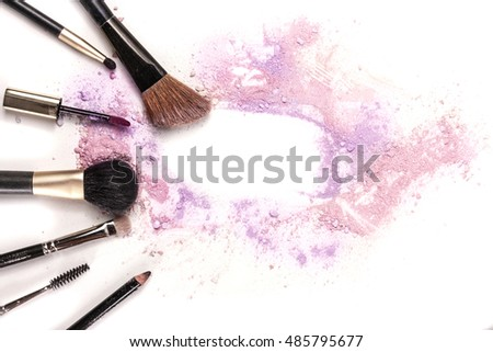 Makeup brushes, lip gloss and pencil on white background, with traces of powder and blush forming a frame. A horizontal template for a makeup artist's business card or flyer design, with copyspace