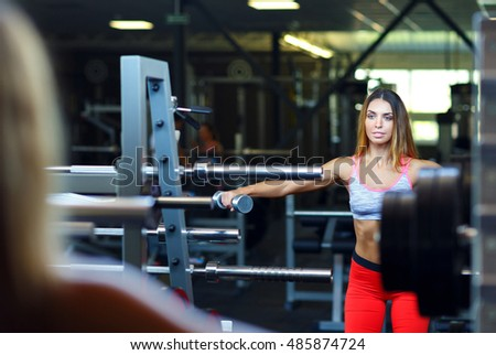 Beautiful slim woman with dumbbell in the gym doing exercises #485874724