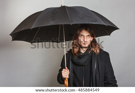 Portrait of handsome fashionable man wearing black coat and scarf holding umbrella. Young guy posing in studio. Winter or autumn fashion. #485884549