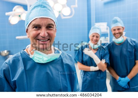 Portrait of surgeon and nurses smiling in operation room at the hospital. Healthcare workers in the Coronavirus Covid19 pandemic  #486034204
