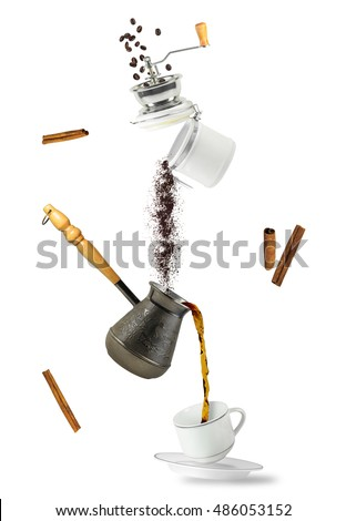 Coffee falling into cup and jezve. Flying coffee grounder. Isolated on white background