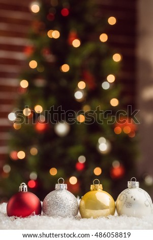 Composite image of Christmas bauble lined up against Christmas tree background #486058819