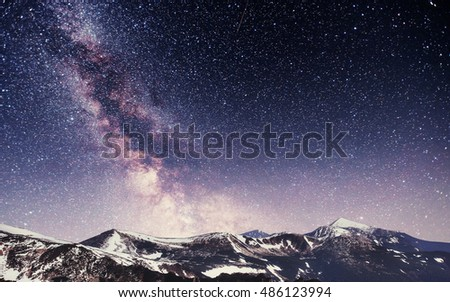 fantastic winter meteor shower and the snow-capped mountains #486123994