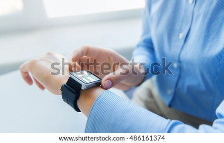 business, technology, online communication and people concept - close up of woman hands with messenger on smart watch screen at office #486161374