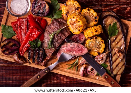 Grilled steak and vegetables on cutting board, top view. Royalty-Free Stock Photo #486217495