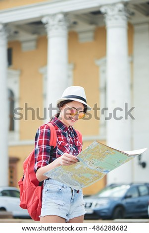 The girl tourist with hat and sunglasses holding a map and looking at her against the building with columns #486288682