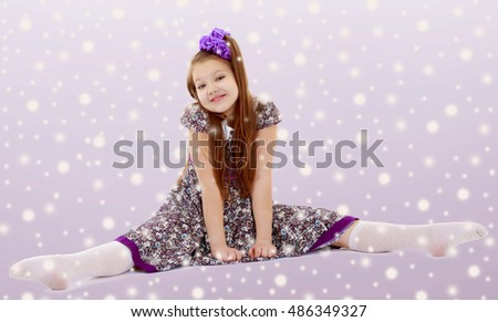 On the Christmas background with white snowflakes.Caucasian little girl with a big purple bow on her head. Girl shows how to do the splits. #486349327