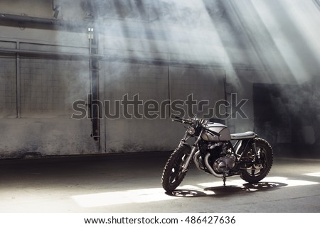 Vintage motorcycle standing in a dark building in the rays of sunlight. Side view Royalty-Free Stock Photo #486427636