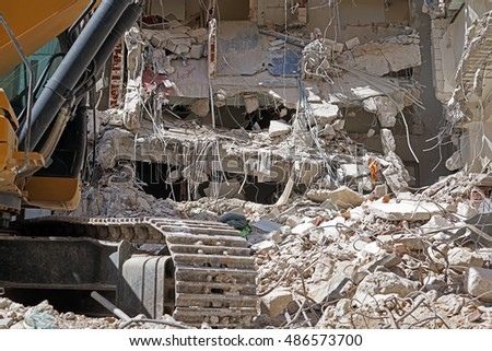 Bulldozer Removes the Debris From Demolition of Old Derelict Buildings on the Construction Site #486573700