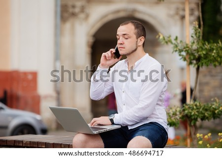 Young businessman sitting in citypark using mobilephone and laptop. #486694717