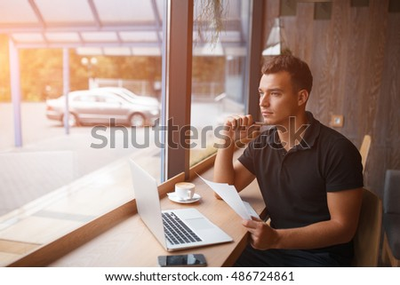 Toned picture of handsome freelance man holding sheet of paper and working in restaurant or cafe with copy space #486724861