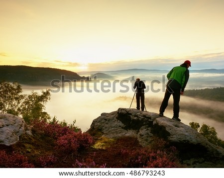 Hiker look down into fogy valley. Photographer stay on cliff and takes photos. Dreamy fogy landscape, blue misty sunrise in a beautiful valley below #486793243