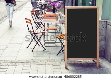 Blank restaurant blackboard on the street with blurry woman pedestrian passing by