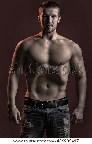 One sexual strong young man with muscular body in jeans looking forward standing posing in studio on red background, vertical picture #486905497