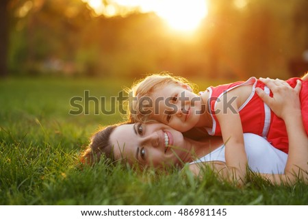 Mother and daughter lying on the lawn. Family in the city park outdoors. Happiness of motherhood and childhood. #486981145