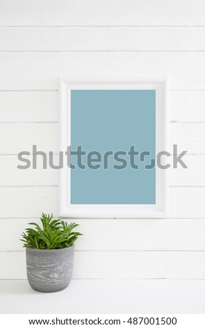 White wooden turquoise background with a plant with a mock up frame for concepts. #487001500