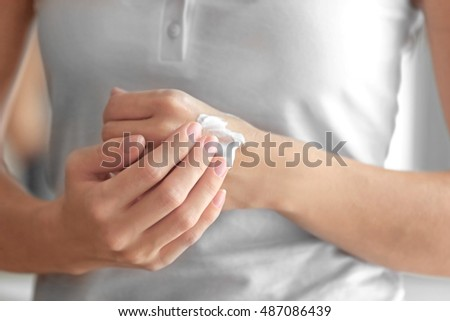 Young woman applying cream onto hands #487086439