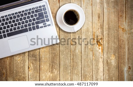 Vintage wood working table with laptop and cup of coffee. Top view with copy space. #487117099