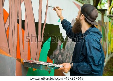 The artist draws graffiti. Royalty-Free Stock Photo #487267645