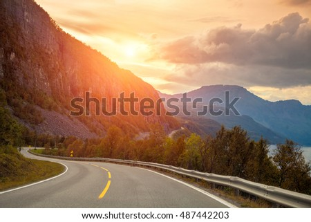 Mountain winding road at sunset. Highway along fjord and rocks. View from windscreen. Beautiful nature of Norway #487442203