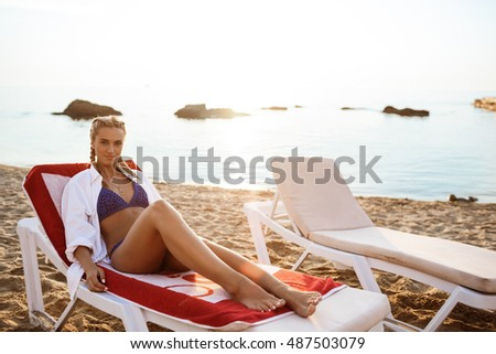 Beautiful blonde girl in swimwear lying on chaise near sea. #487503079
