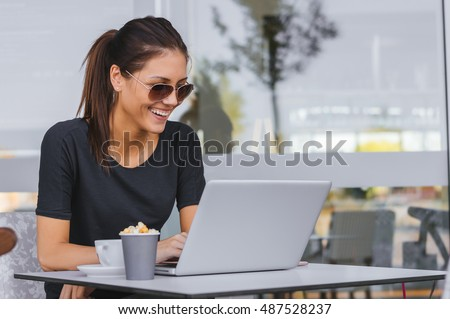 Charming woman with beautiful smile reading good news during rest in coffee shop, happy Caucasian female watching her photos and smiling, while relaxing in cafe during free time #487528237