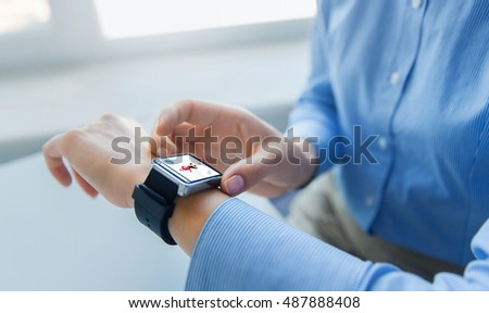 business, technology, sport and people concept - close up of woman hands setting smart watch with fitness application at office #487888408