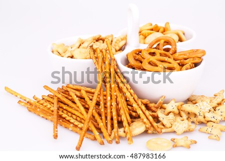 Different salted crackers in bowl isolated on white background. #487983166
