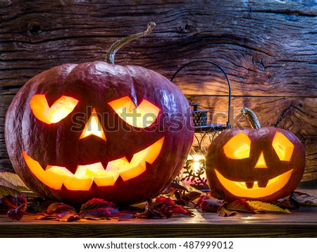 Grinning pumpkin lantern or jack-o'-lantern is one of the symbols of Halloween. Halloween attribute. Wooden background. #487999012