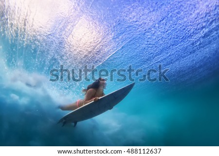 Sportive girl in bikini in action. Surfer with surf board dive underwater under breaking ocean wave. Healthy lifestyle. Water sport, swim and extreme surfing in adventure camp on summer beach vacation #488112637