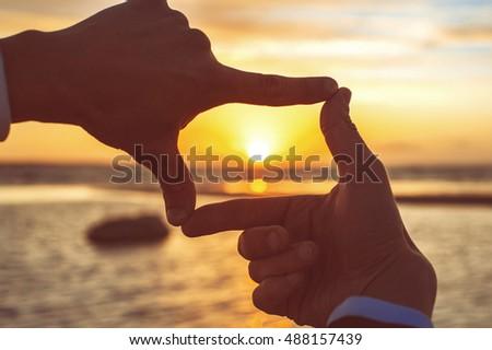Composition finger frame- man's hands capture the sunset on backlit on background. Multicolored horizontal outdoors image with vintage filter